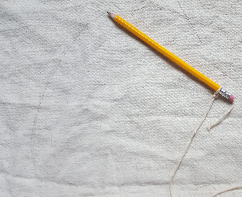 Slipcovered ottoman in white pencil