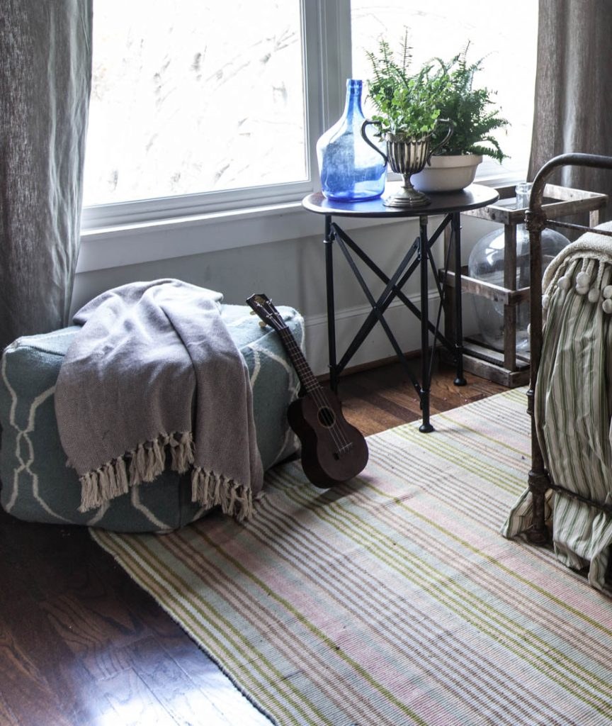 striped rug and green bed and window