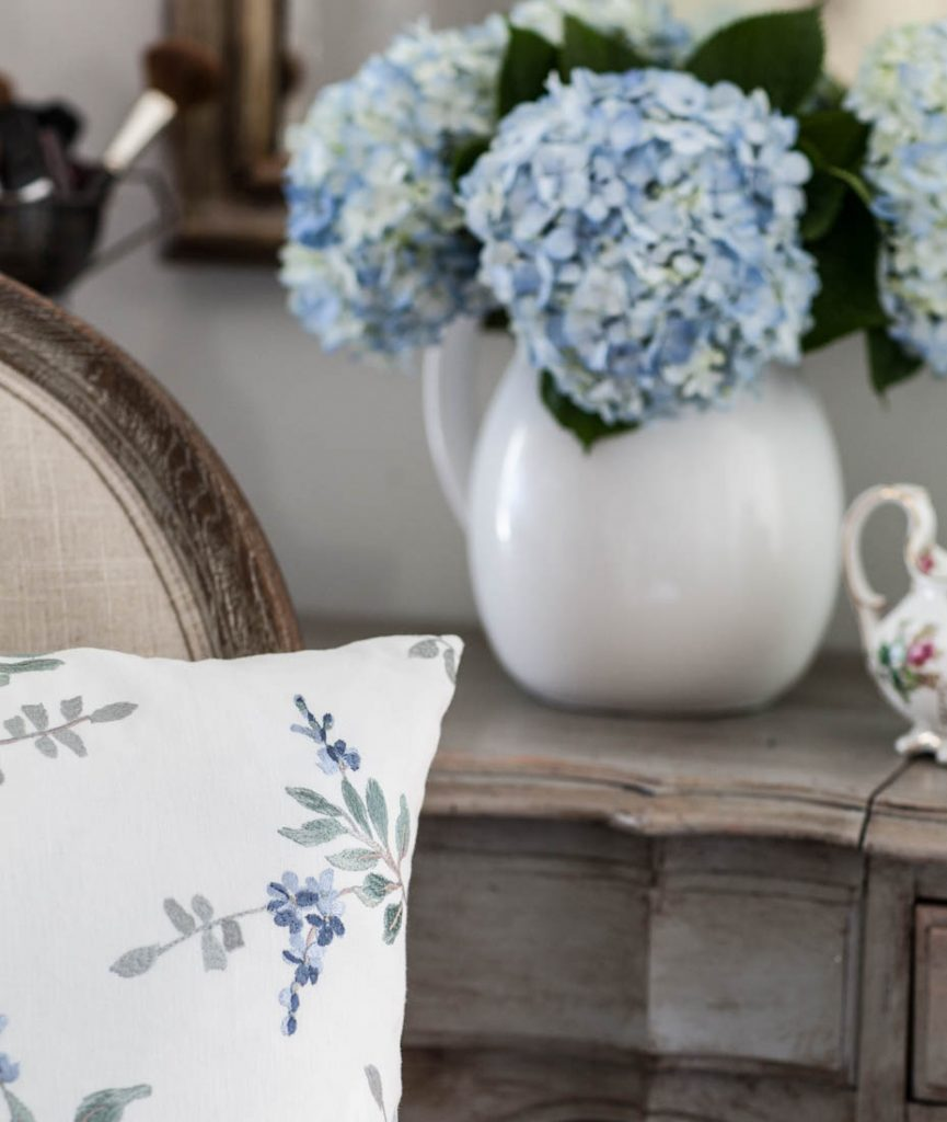 blue floral embroidery pillow and hydrangeas