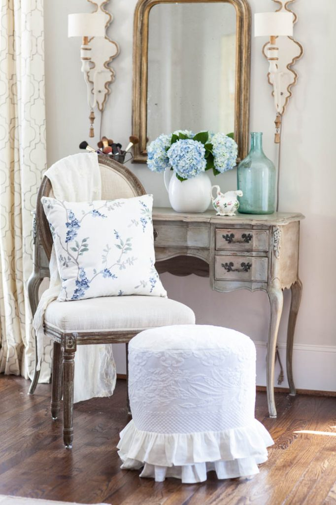 blue floral embroidery pillow on chair by vanity