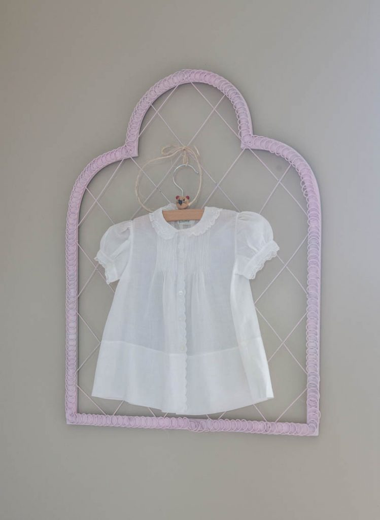 pink curtains behind bed and little dresses