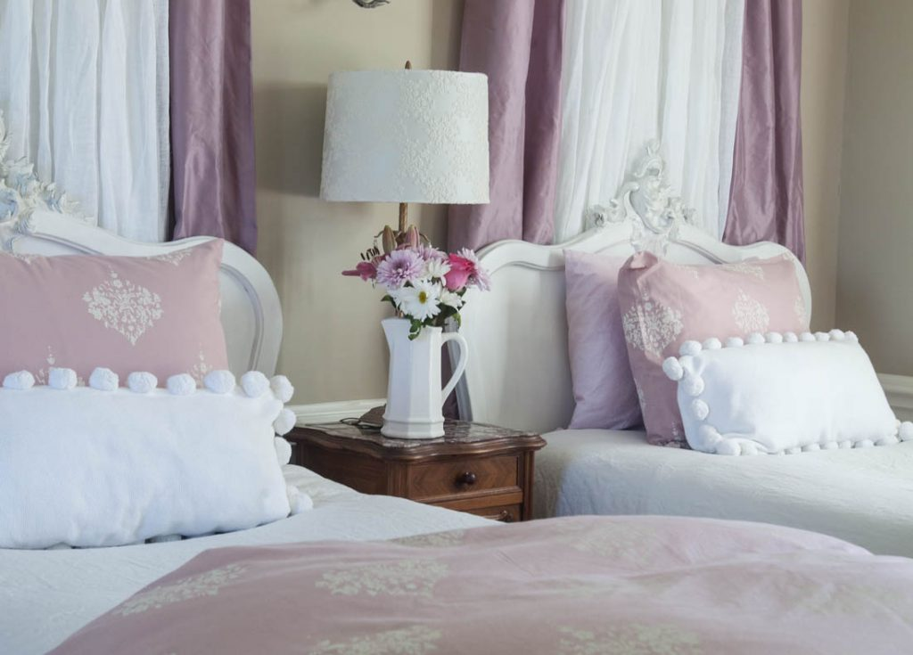 pink curtains behind bed and flowers